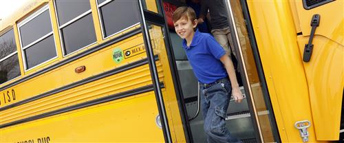 Boy exiting bus